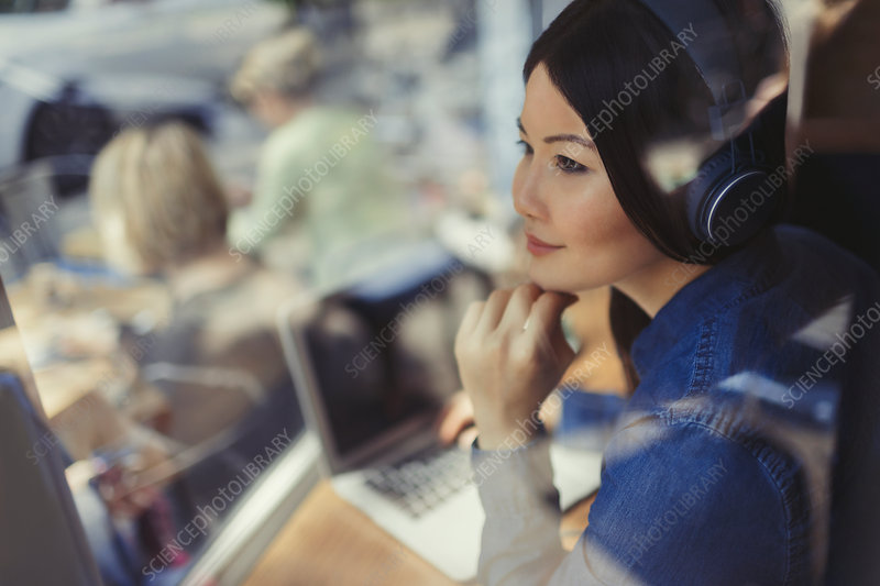 Pensive woman at laptop listening to music