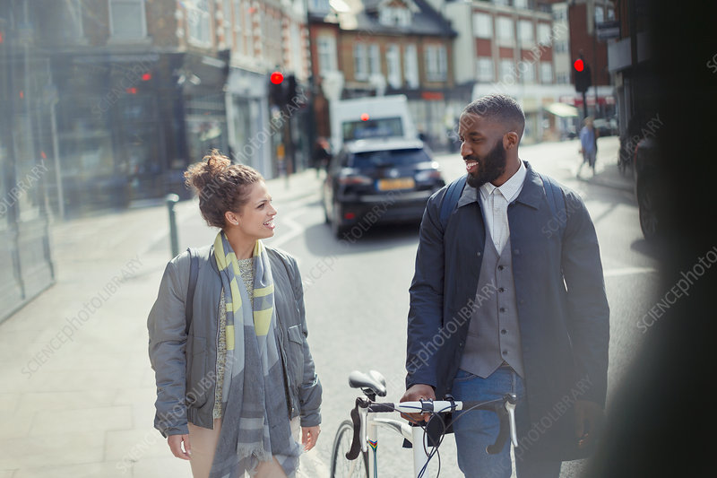 Couple walking, commuting with bicycle