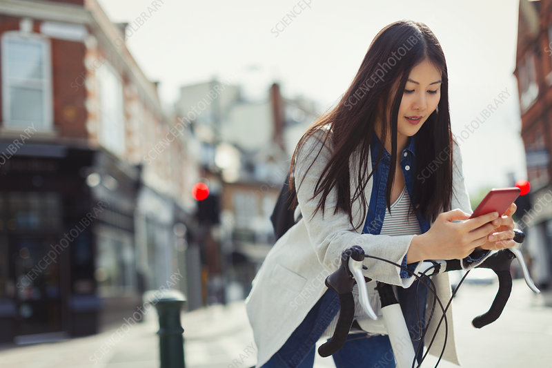 Young woman commuting on bicycle, texting