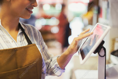 Female cashier using touch screen cash register