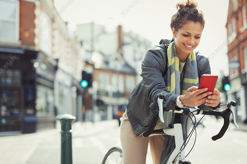 Smiling woman commuting with bicycle, texting