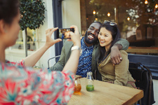 Woman photographing affectionate couple friends
