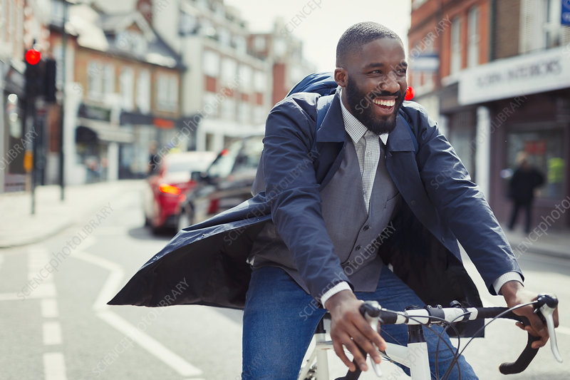 Smiling businessman commuting, riding bicycle