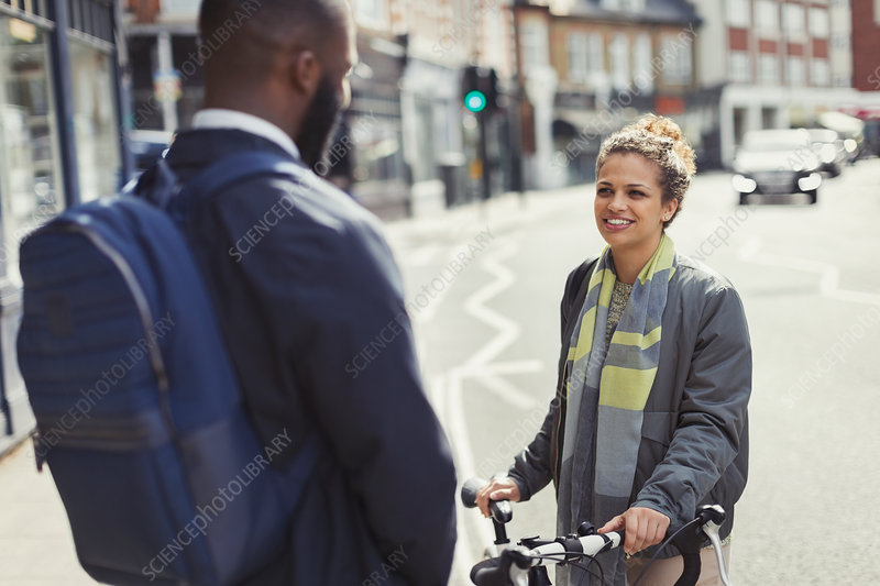 Friends with bicycle talking on sunny urban street