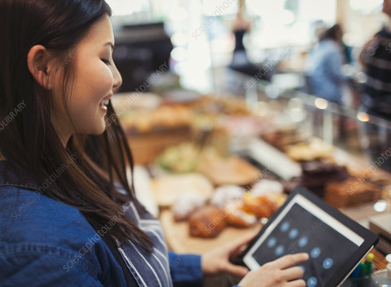Smiling cashier using touch screen cash register