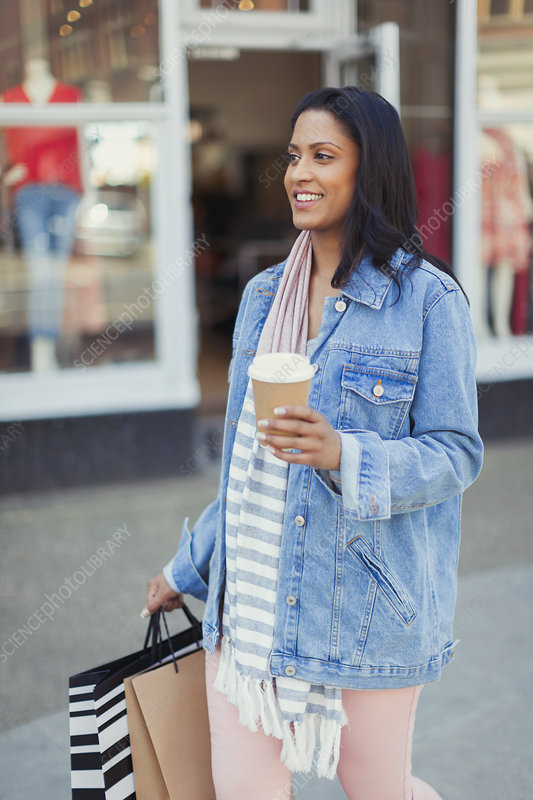 Smiling woman walking along storefront