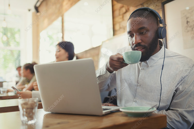 Man using laptop and drinking coffee in cafe