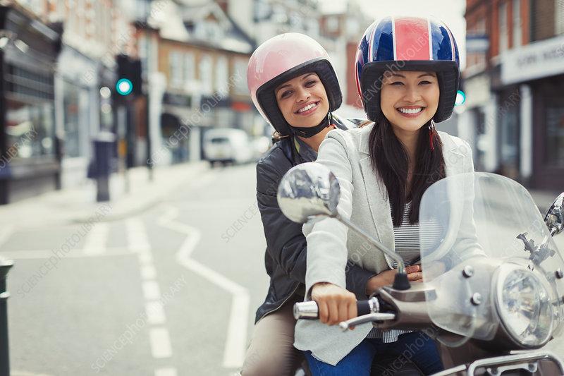 Smiling women riding motor scooter