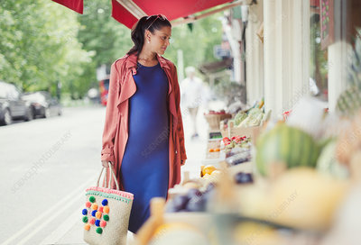 Pregnant woman shopping for produce