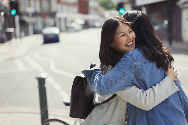Smiling affectionate female friends hugging