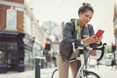 Young woman texting , commuting on bicycle