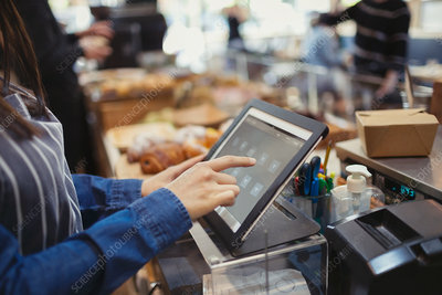 Cashier using touch screen cash register in cafe