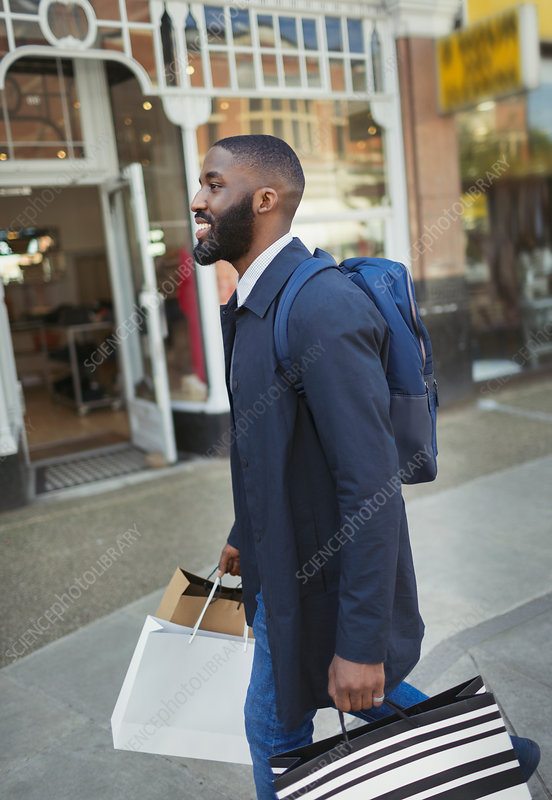 Smiling man walking along storefront