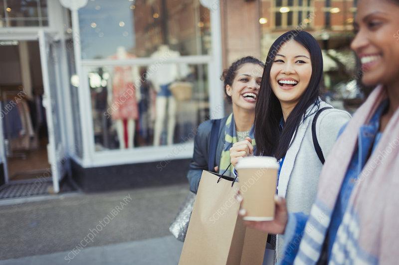 Laughing women friends walking along storefront