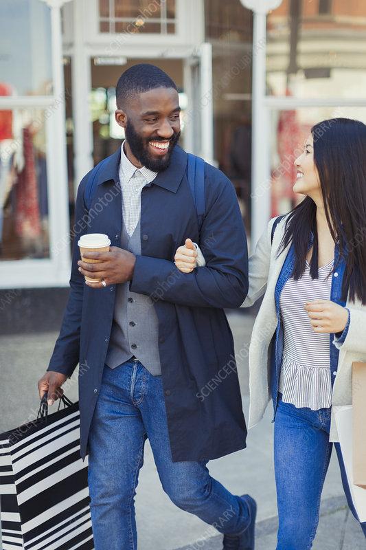 Smiling couple walking along storefront