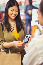 Female shopper with credit card using touchless