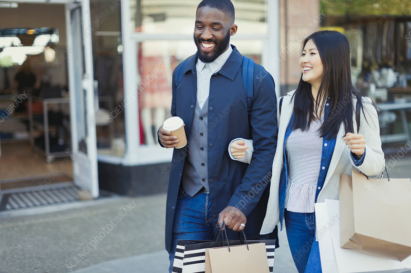 Smiling couple walking arm in arm along storefront