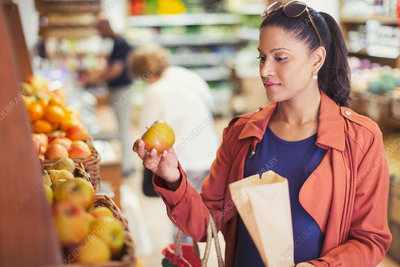Woman shopping, examining apple in grocery store
