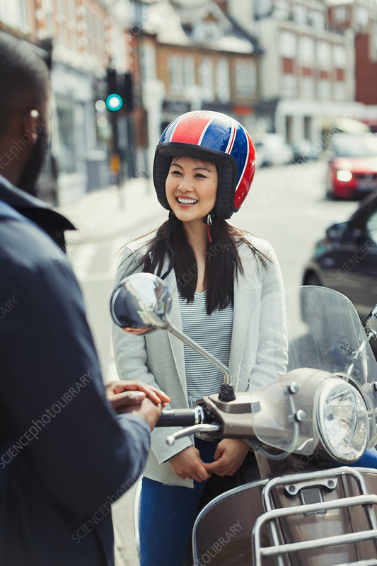 Smiling woman in helmet on motor scooter