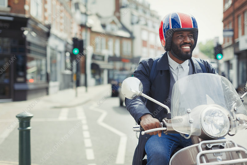 Smiling businessman in helmet riding motor scooter