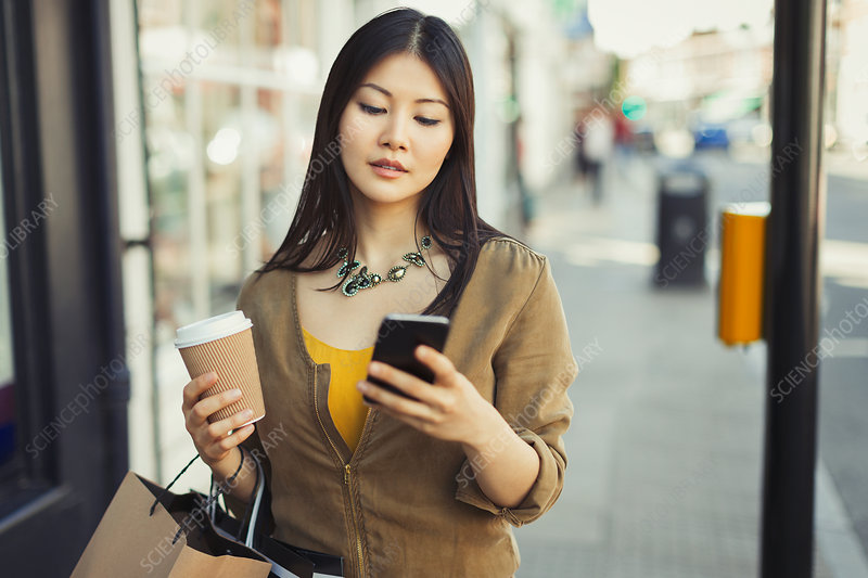 Young woman with coffee texting on urban sidewalk