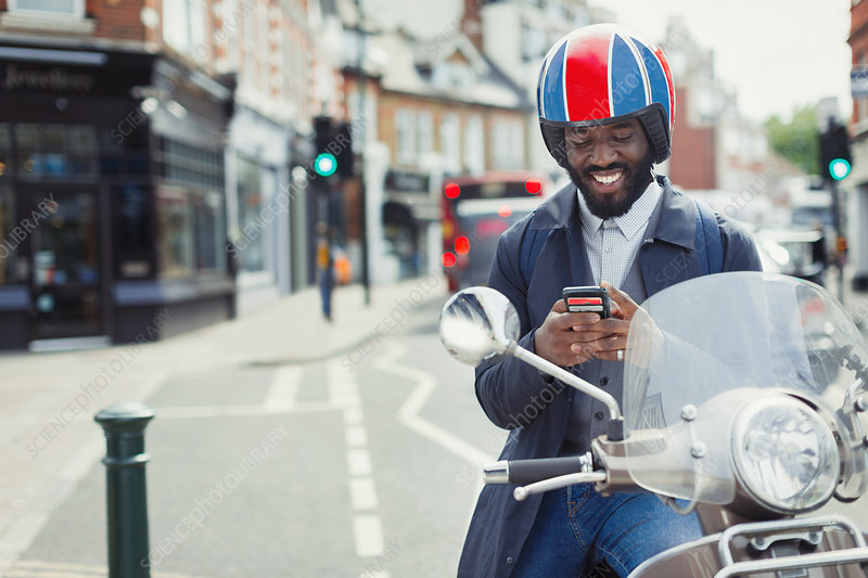 Smiling businessman on motor scooter texting