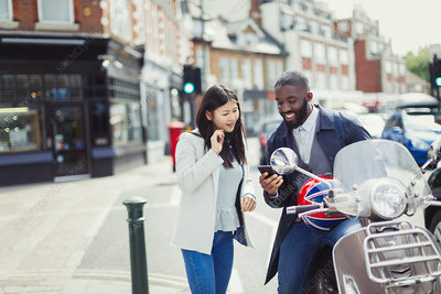 Young couple using cell phone at motor scooter