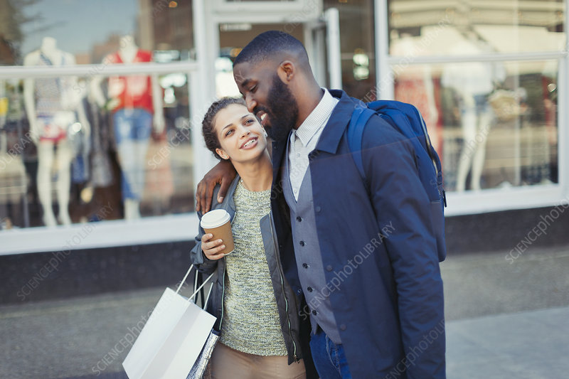 Affectionate couple with coffee and shopping bag