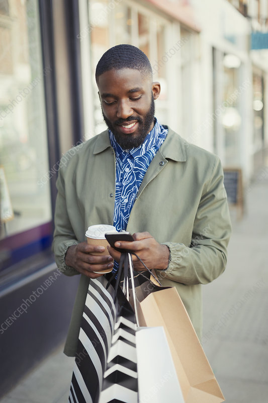 Smiling man texting on urban sidewalk