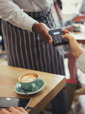 Customer paying waiter with credit card reader
