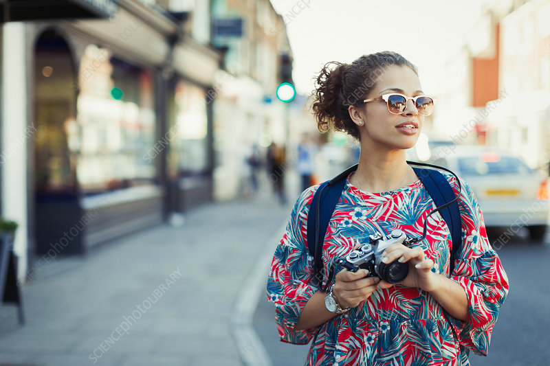Young female tourist in sunglasses with camera