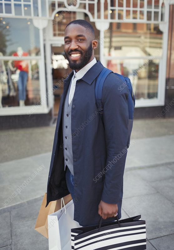 Portrait man with shopping bags outside storefront