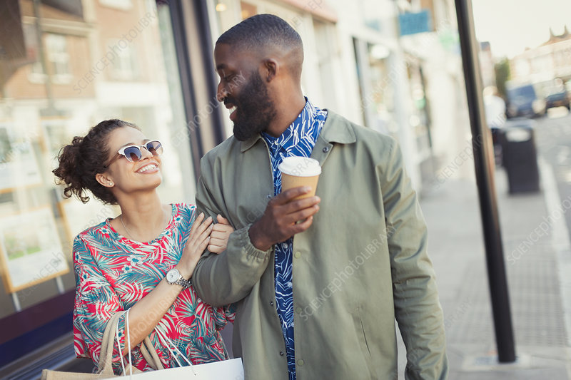 Smiling couple with coffee walking arm in arm