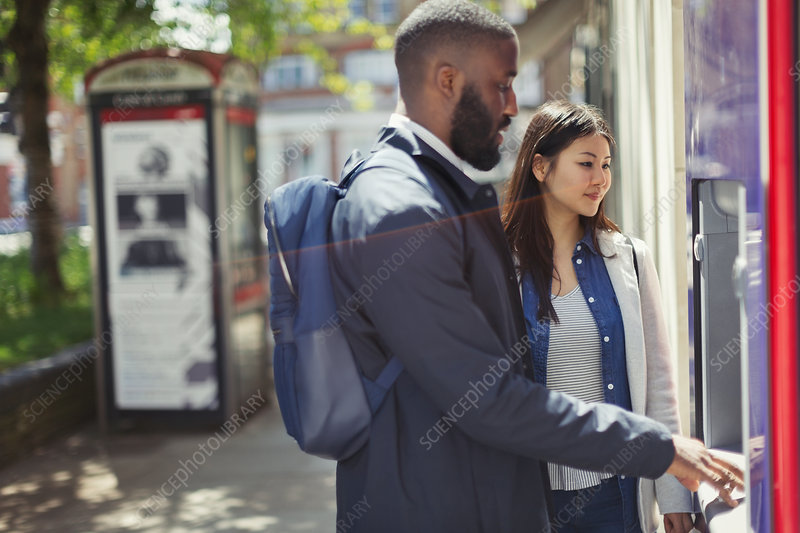 Young couple using urban ATM