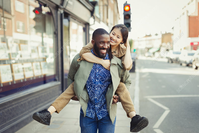 Playful couple piggybacking on urban street