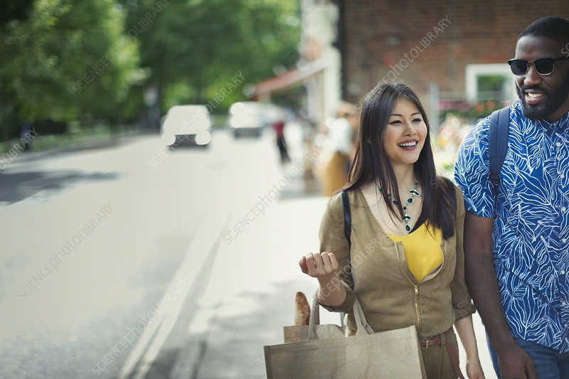 Smiling couple with shopping bag walking