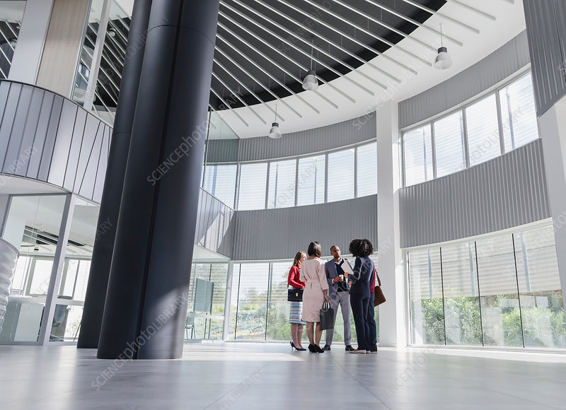 Business people talking in modern office lobby