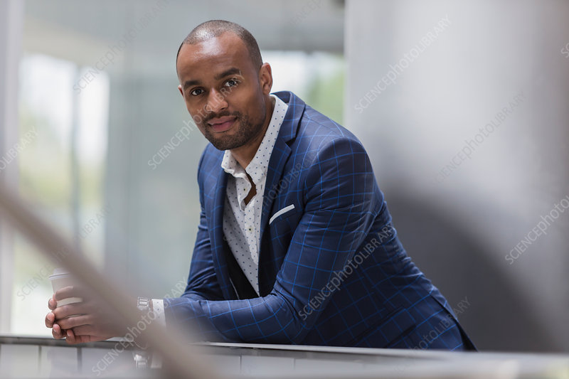 Portrait confident businessman leaning on railing