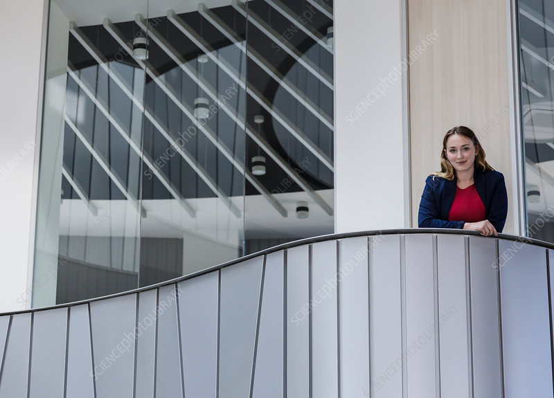 Businesswoman standing on modern office balcony
