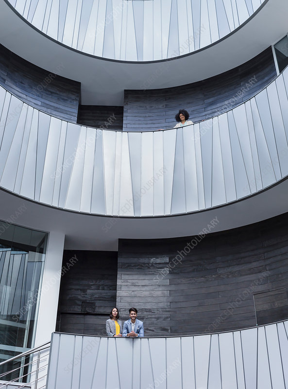 Business people standing on modern balconies