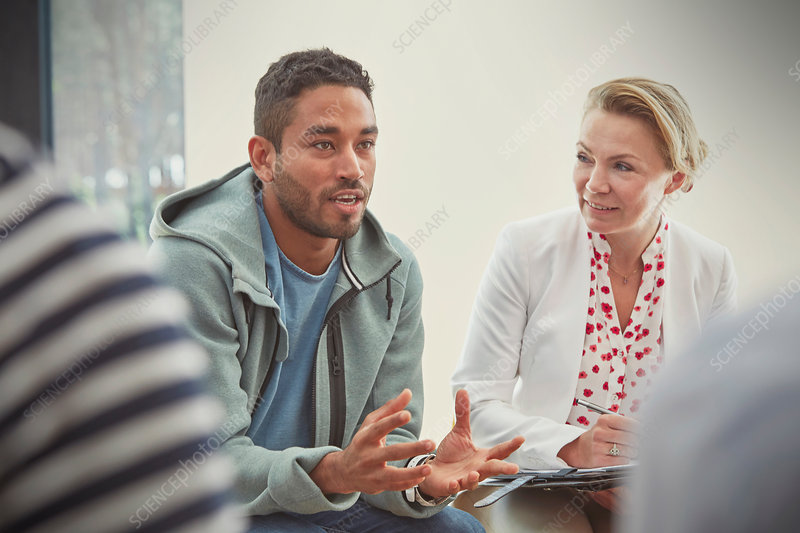Young man talking in group therapy session