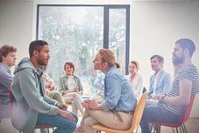 Group watching man and woman in group therapy