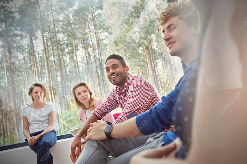 Smiling people listening in group therapy session