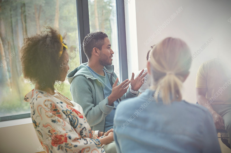 Man talking and gesturing in group therapy session