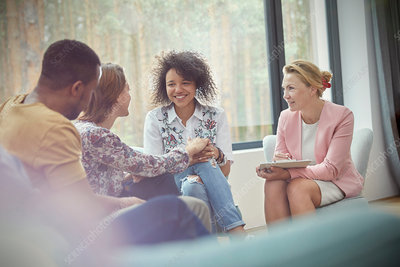 Smiling woman comforting woman in group therapy