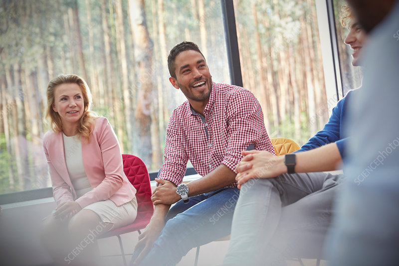 Smiling man listening in group therapy session