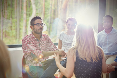 Attentive man listening to woman in group therapy