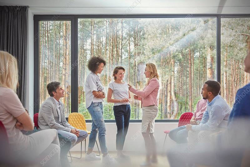 Women standing and talking in group therapy