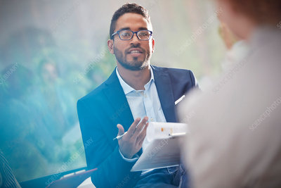 Man with clipboard talking in meeting