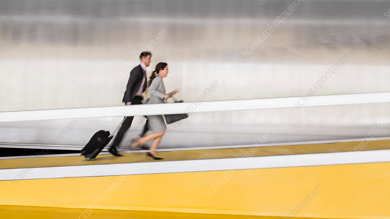Business people running up airport ramp